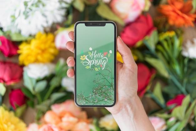 Mano sujetando maqueta de smartphone encima de flores PSD gratuito
