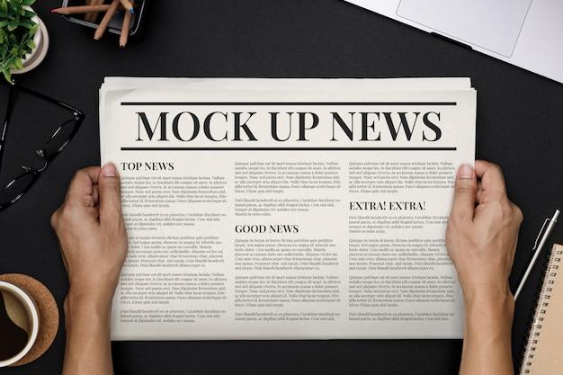 Manos sosteniendo business newspaper con plantilla de maqueta de espacio de copia en topview escritorio negro PSD Premium
