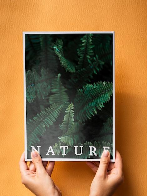 Manos sosteniendo una revista de naturaleza sobre un fondo naranja PSD gratuito