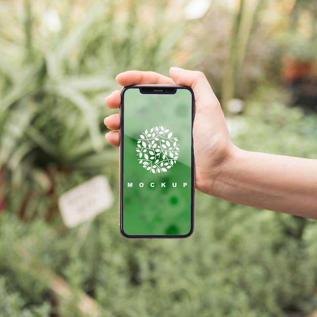 Mão, segurando, smartphone, mockup, com, jardinagem, conceito Psd grátis