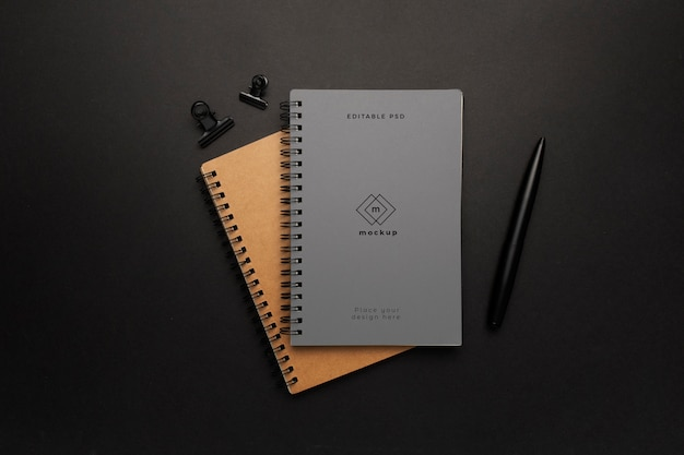 Maqueta de cuadernos con elemento negro sobre fondo negro PSD gratuito