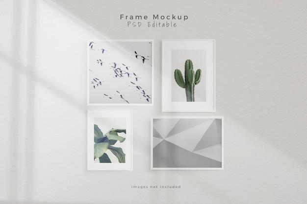 Maqueta de cuatro marcos de fotos vacíos en una habitación vacía de pared blanca PSD gratuito