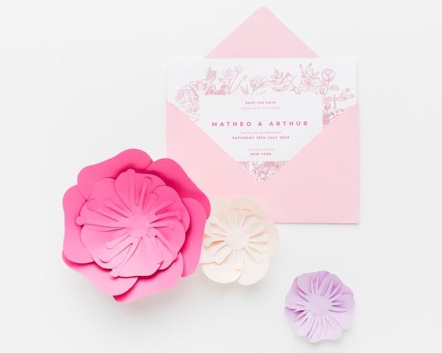 Maqueta de invitación de boda con flores de papel sobre fondo blanco. PSD gratuito
