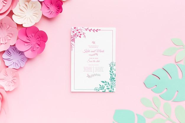 Maqueta de invitación de boda con flores de papel sobre fondo rosa PSD gratuito