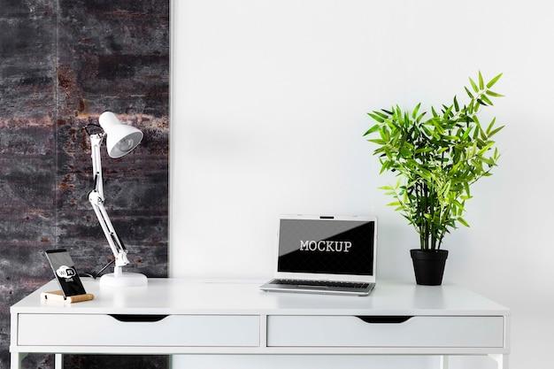 Maqueta de laptop en escritorio moderno PSD gratuito