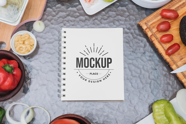 Maqueta de libro de recetas rodeado de verduras PSD gratuito