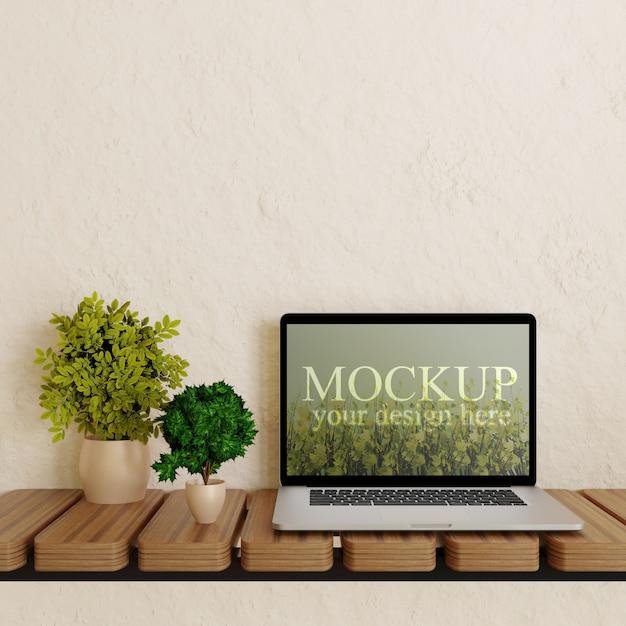 Maqueta de la pantalla del portátil en el escritorio de pared de madera con plantas PSD Premium