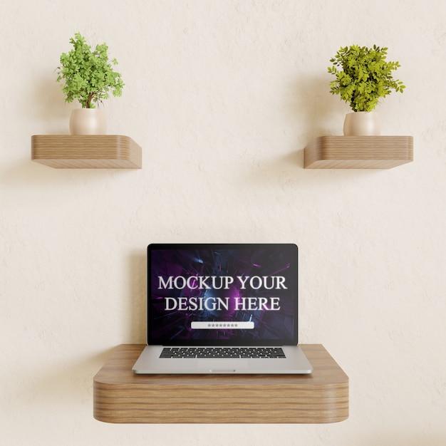 Maqueta del portátil en el escritorio de pared con decoración de plantas par PSD Premium