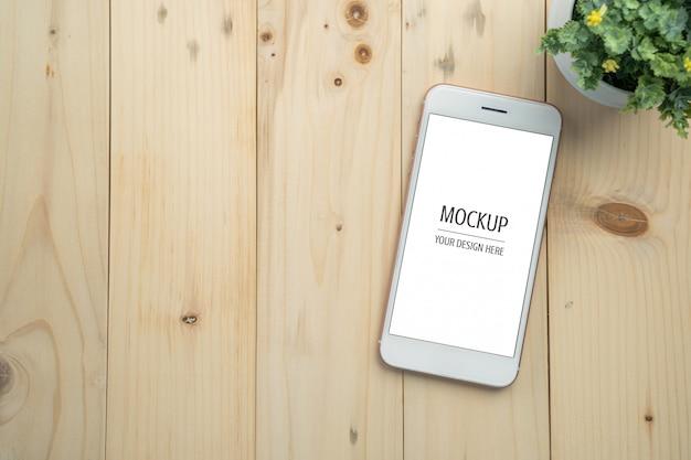 Maqueta de smartphone de pantalla blanca en blanco en mesa de madera PSD Premium