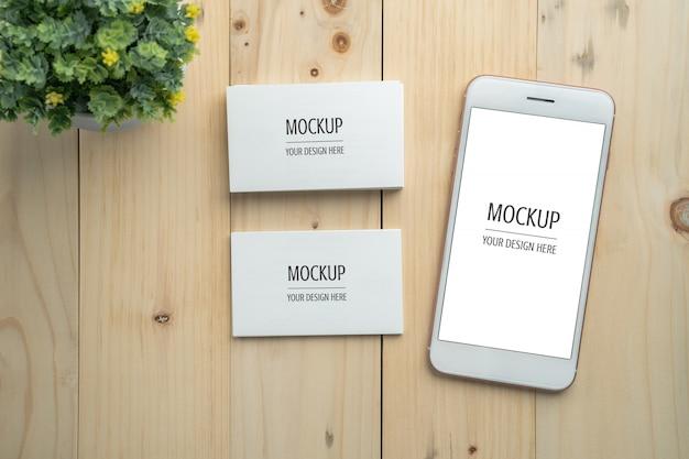 Maqueta de smartphone y tarjeta de visita de pantalla blanca en blanco en mesa de madera PSD Premium