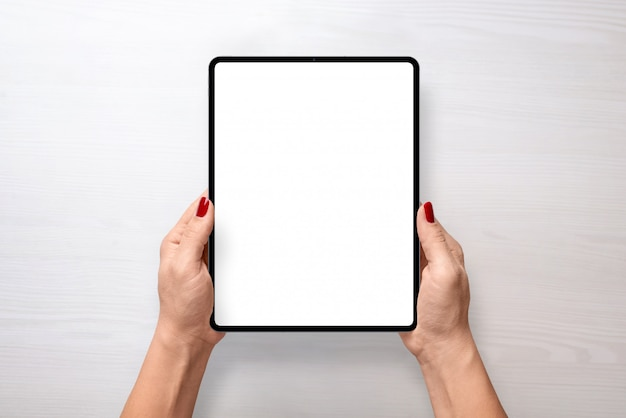 Maqueta de tableta digital en mujer manos vista superior posición vertical PSD Premium