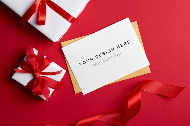 Maqueta de tarjeta de felicitación con cajas de regalo sobre fondo rojo. PSD Premium