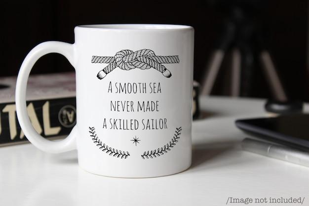Maqueta de una taza de café de cerámica blanca sobre una mesa PSD Premium