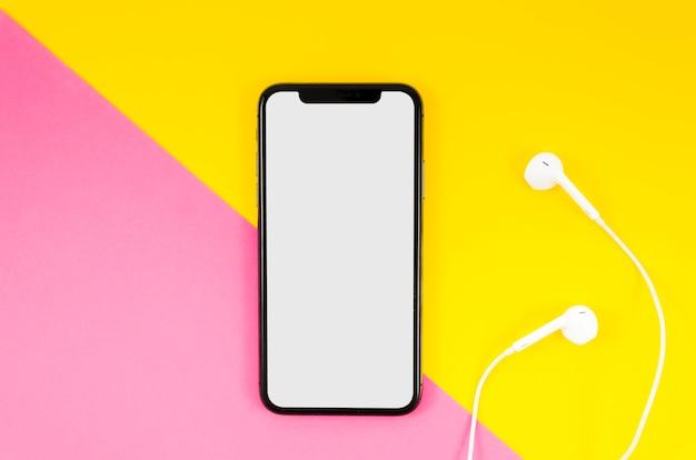 Maqueta de teléfono inteligente de vista superior con auriculares PSD gratuito