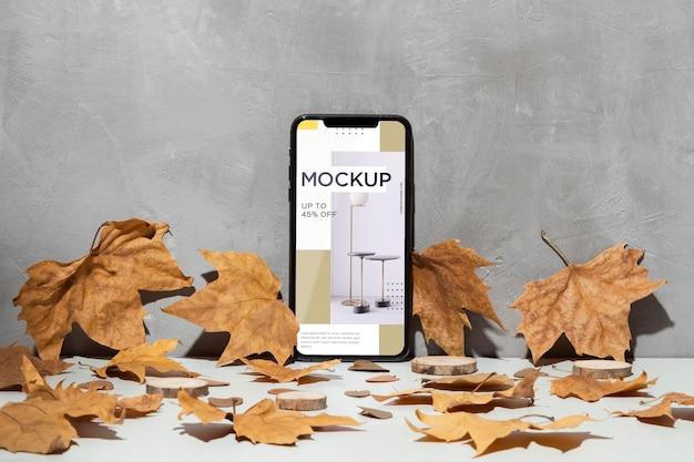 Maqueta de teléfono móvil apoyado en la pared rodeada de hojas PSD gratuito