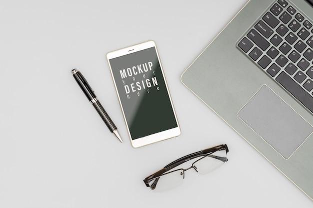 Maqueta de teléfono móvil en la mesa de escritorio de oficina PSD Premium