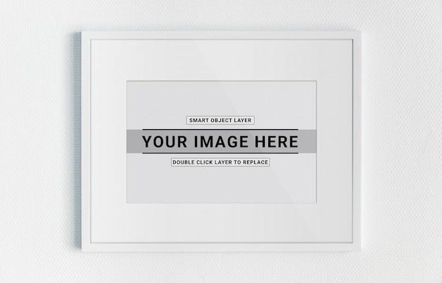 Marco blanco colgado en una maqueta de pared blanca PSD Premium