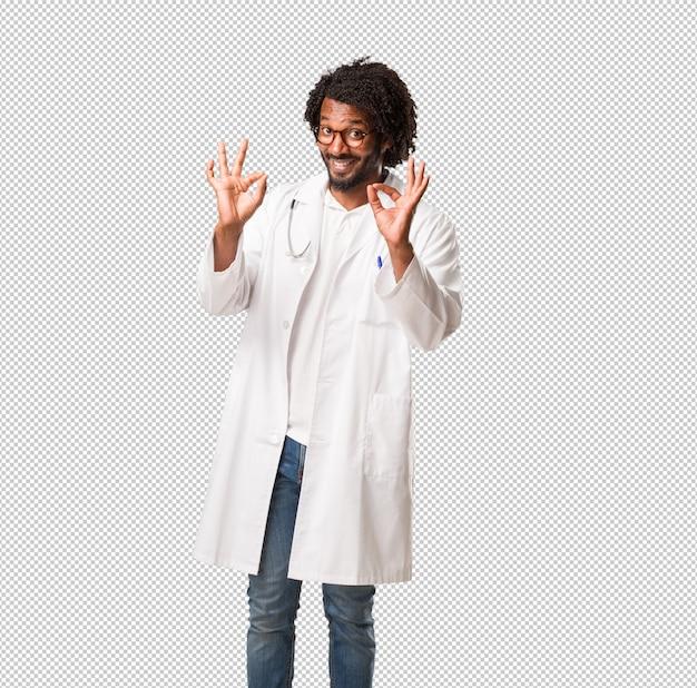 Medico afroamericano bello allegro e sicuro che fa gesto giusto, eccitato e che grida, concetto di approvazione e successo Psd Premium