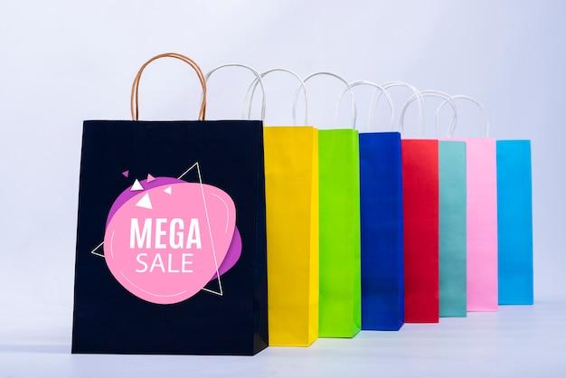Mega verkoopbanner met kleurrijke papieren zakken Gratis Psd