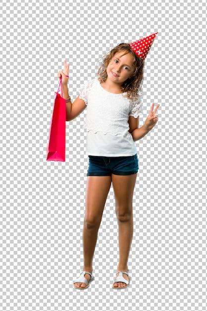 Meisje bij een verjaardagspartij die een giftzak houdt glimlachend en tonend overwinningsteken Premium Psd