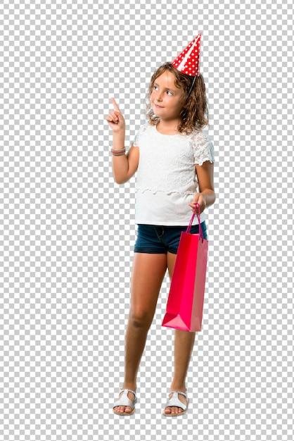 Meisje bij een verjaardagspartij die een giftzak houdt richtend met de wijsvinger een groot idee Premium Psd