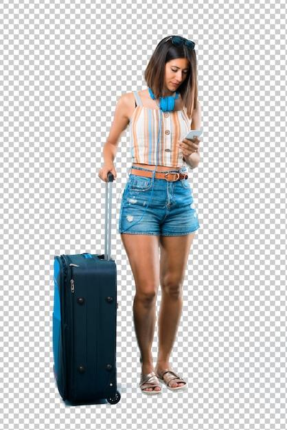 Meisje dat met haar koffer reist die een bericht of e-mail met mobiel verzendt Premium Psd