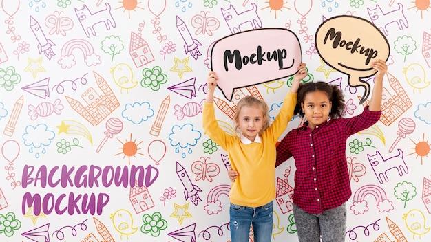Meisje en jongen houden mock-up praatjebellen Gratis Psd