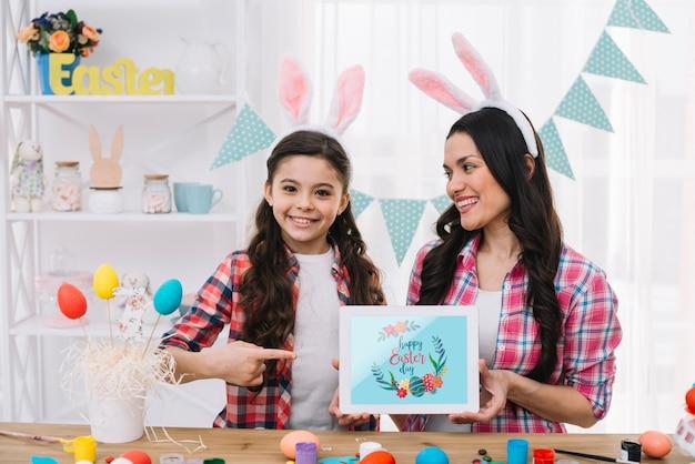 Meisje en moeder met tabletmodel op pasen-dag Gratis Psd