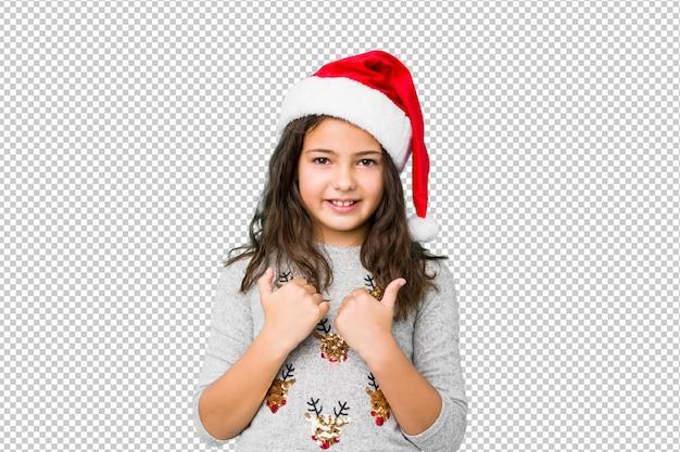 Meisje het vieren kerstmisdag die beide duimen omhoog opheft, glimlachend en zeker. Premium Psd