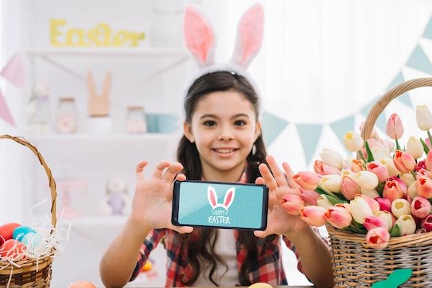 Meisje met smartphonemodel op pasen-dag Gratis Psd
