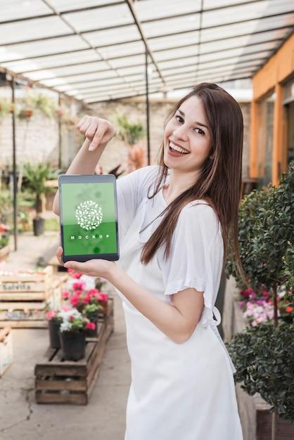 Meisje met tablet-mockup met tuinieren concept Gratis Psd