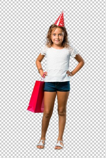 Meisje op een verjaardagsfeestje met een geschenk tas poseren met armen op heup Premium Psd