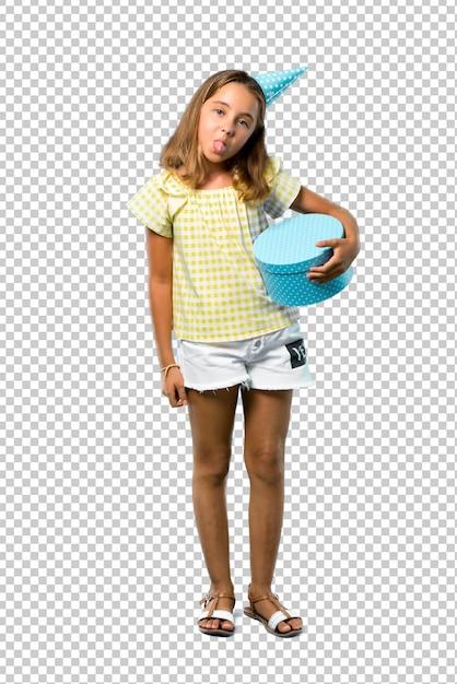 Meisje op een verjaardagspartij die een gift houdt die tong toont bij de camera die grappige blik hebben Premium Psd