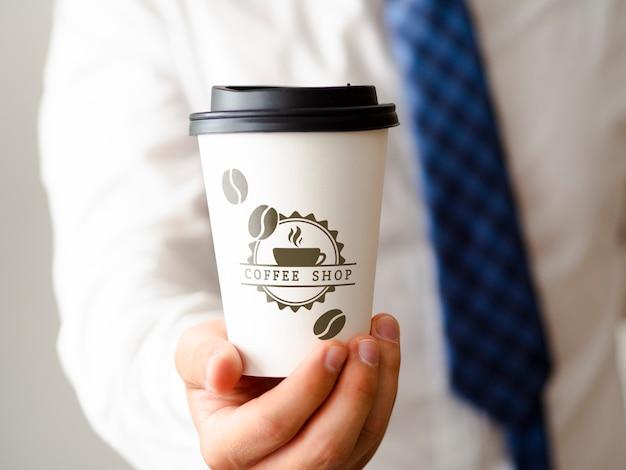 Mens die een kop van koffiemodel houdt Gratis Psd