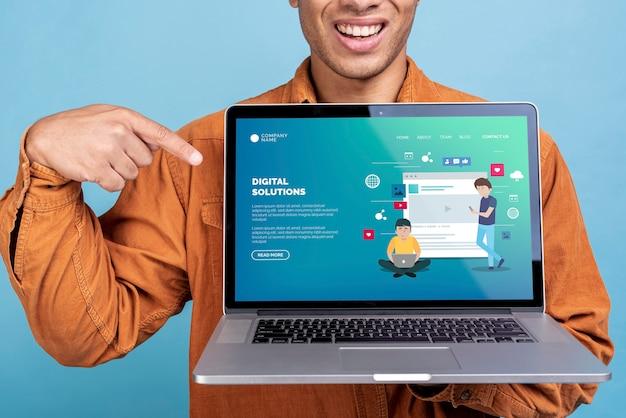 Mens die laptop met een digitale oplossingslandingspagina houdt Gratis Psd