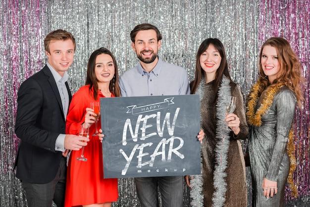 Mensen die bord houden voor het nieuwe jaar Gratis Psd
