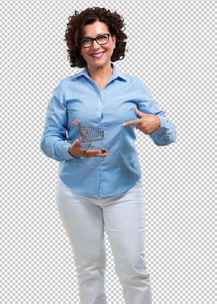 Midden oude en glimlachende vrouw die, een miniatuurboodschappenwagentje, concept het winkelen, consumentisme houden glimlachen Premium Psd