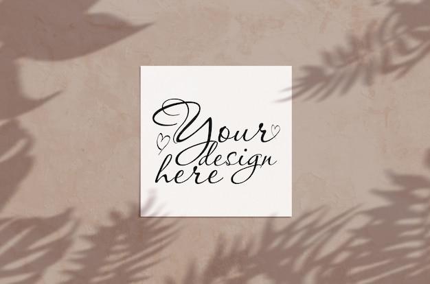 Minimale zomer plat lag bovenaanzicht vierkante kaart mockup op lichtbruine kleur grond met tropische palm leves schaduw Premium Psd