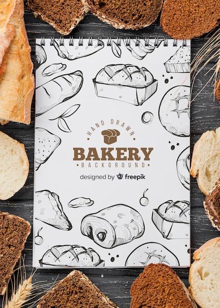 Mock-up cornice di pane con il taccuino Psd Gratuite