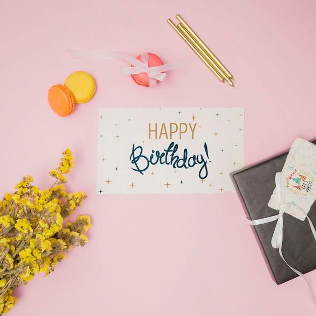 Mock-up di buon compleanno con carta di invito e fiori Psd Gratuite
