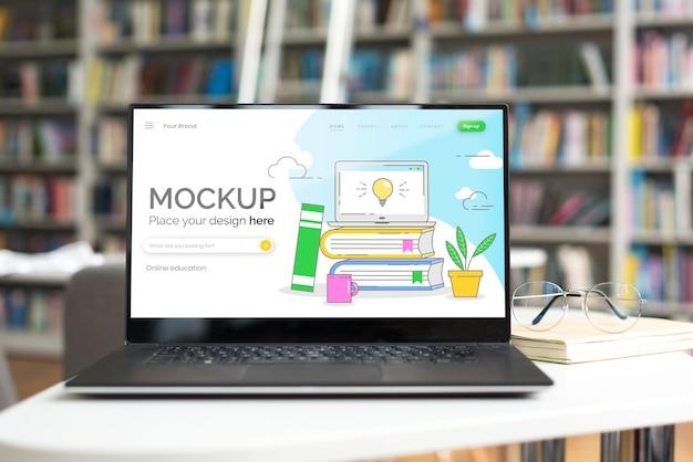 Mock-up laptop op tafel in bibliotheek Gratis Psd