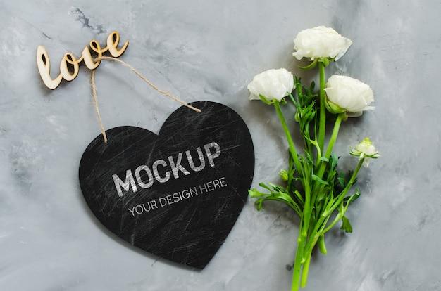 Mock up van de wenskaart. leeg schoolbordhart dat met bloemen en inschrijvingsliefde wordt gevormd. Premium Psd