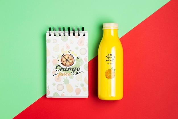 Mock-upblocnote en plastic fles met smoothie Gratis Psd