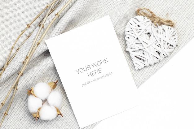 Mockup-ansichtkaart met houten hart en katoen Premium Psd