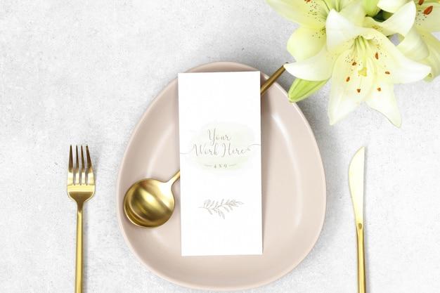 Mockup bruiloft menu met gouden bestek en lelies Premium Psd