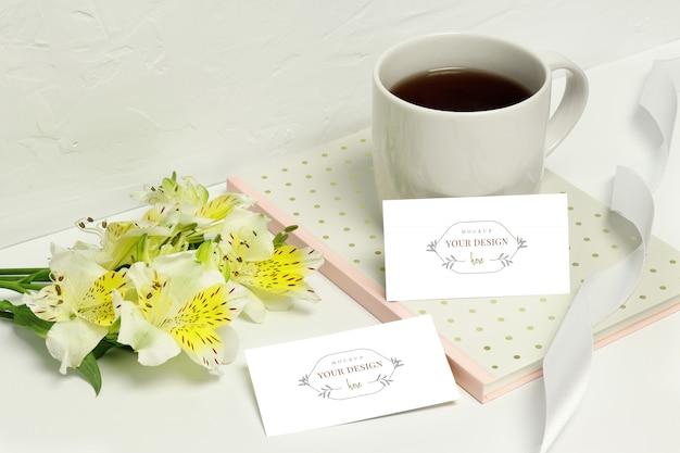Mockup carte di carta su sfondo bianco con bellissimi fiori, note, nastro e tazza di caffè Psd Premium