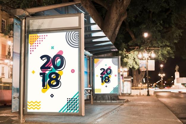 Mockup de cartel de parada de autobús en ciudad de noche PSD gratuito