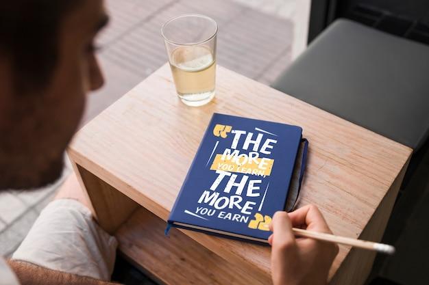 Mockup de cover de libro enfrente de hombre joven PSD gratuito