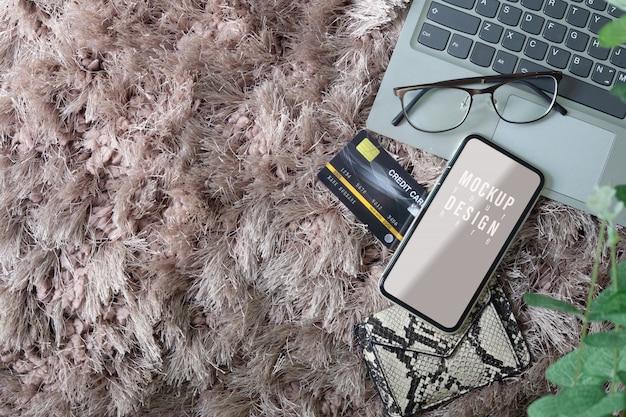 Mockup del telefono cellulare schermo vuoto con laptop, occhiali e carta di credito Psd Premium