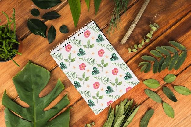 Mockup di blocco note con foglie tropicali Psd Gratuite
